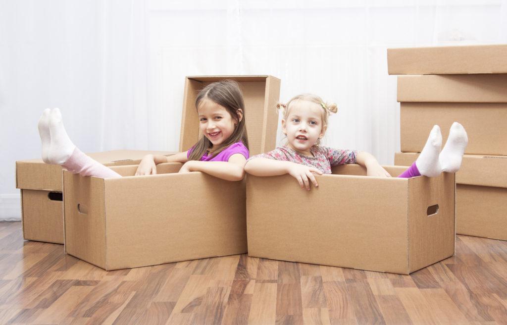 girls sitting in public storage unit boxes