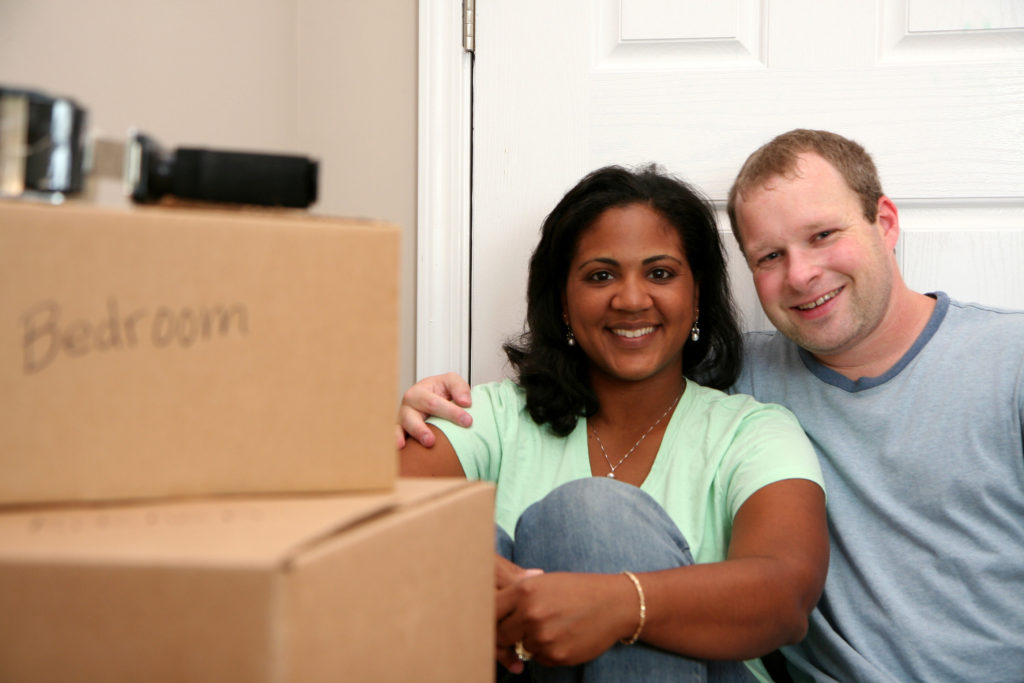 Family following storage tips while moving boxes into a storage unit
