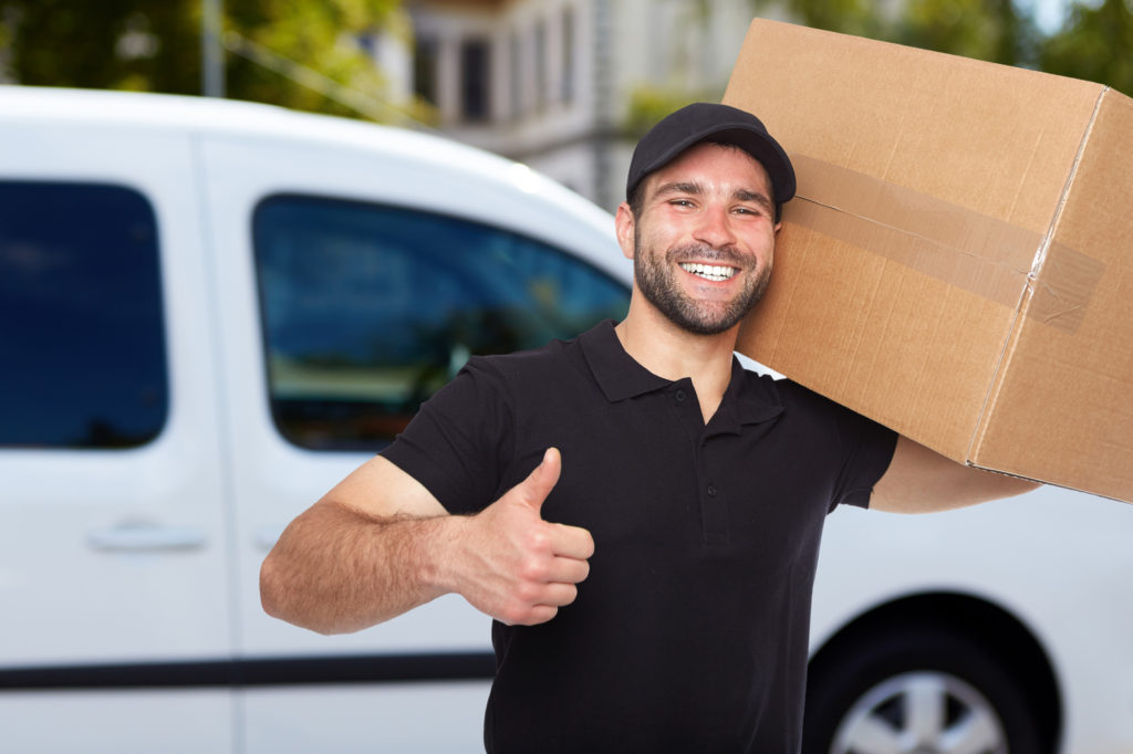 Smiling man carrying a storage box
